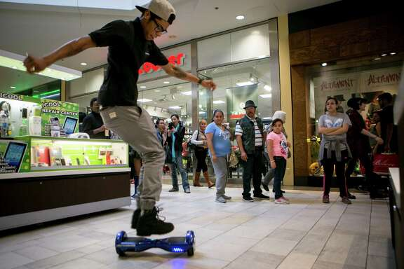 Shannon Clay Jr. performs tricks on a Power Board, a type of hoverboard he sells at a mall kiosk in Austin. Three airlines have decided to ban hoverboards from flights because of the potential fire danger from lithium batteries.