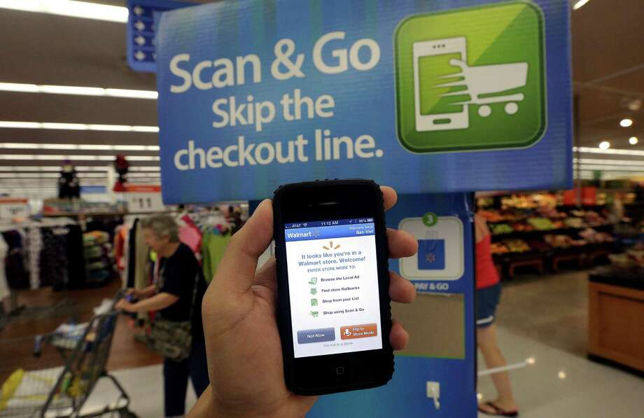 In 2013, a Wal-Mart representative demonstrated a Scan & Go mobile application on a smartphone at a store in San Jose, Calif. Wal-Mart is now trying to develop its own electronic pay system and is still part of another project involving other retailers. Photo: Jeff Chiu, STF / AP