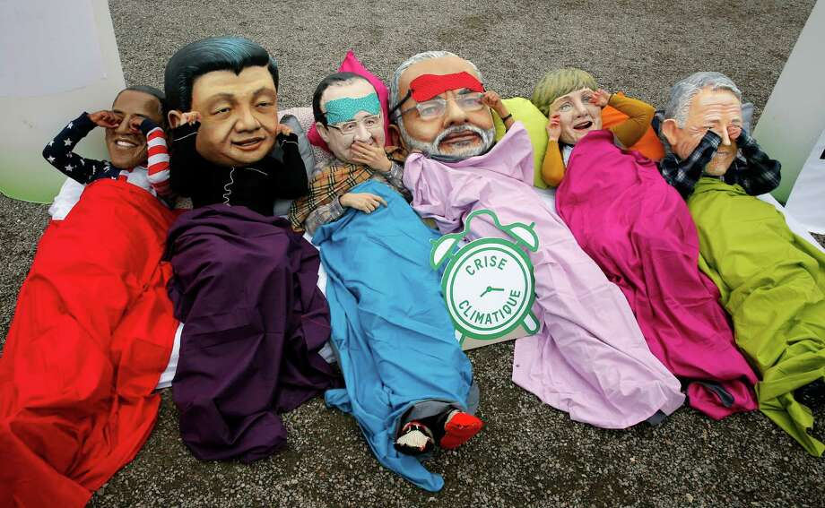 """Oxfam activists act out the proverb """"see no evil, hear no evil, speak no evil"""" while wearing masks of world leaders during a protest Thursday at the climate conference. Photo: Christophe Ena, STF / AP"""