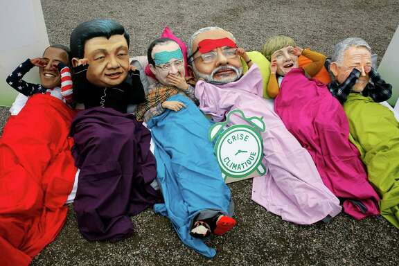 """Oxfam activists act out the proverb """"see no evil, hear no evil, speak no evil"""" while wearing masks of world leaders during a protest Thursday at the climate conference."""