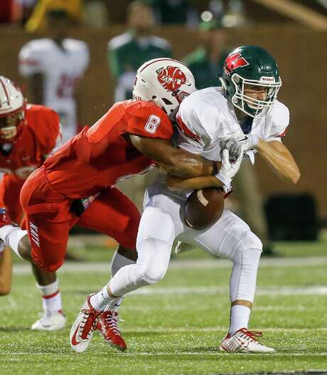 The Woodlands quarterback Eric Schmid has the ball stripped by Katy's JoVanni Stewart. The Tigers' stingy defense allows a mere 3.9 points and 158.1 yards per game. Photo: Bob Levey, Photographer / ©2015 Bob Levey