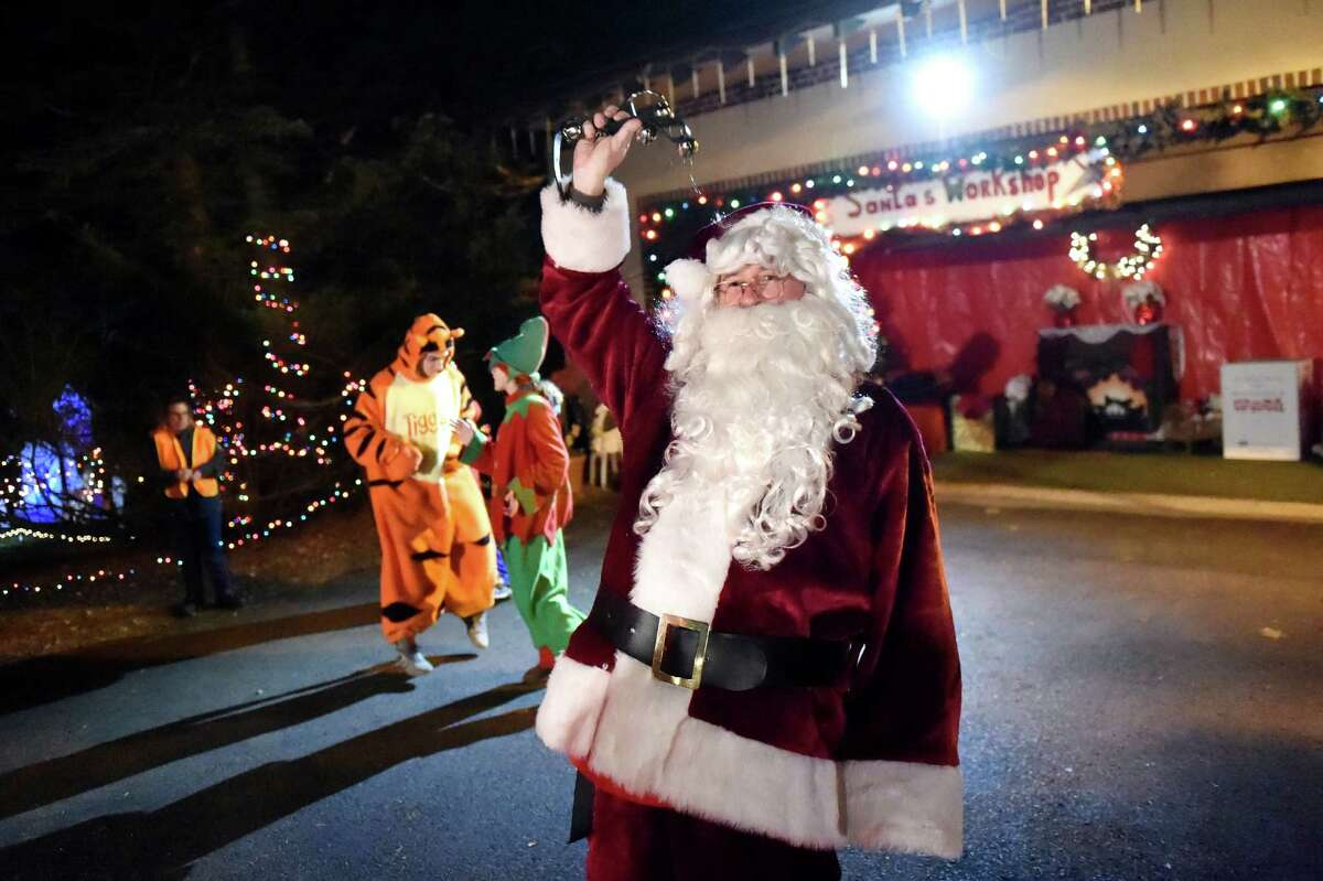 Santa and friends greet carloads of spectators during the 17th annual Light up the Sky with the Marching Rams holiday light display on Thursday, Dec. 10, 2015, at 154 Brookside Ave. in Amsterdam, N.Y. The show runs through Dec. 23 from 6:30 to 9 p.m., weather permitting. The cost is $5 per vehicle with all proceeds benefitting the Amsterdam High marching band. (Cindy Schultz / Times Union)