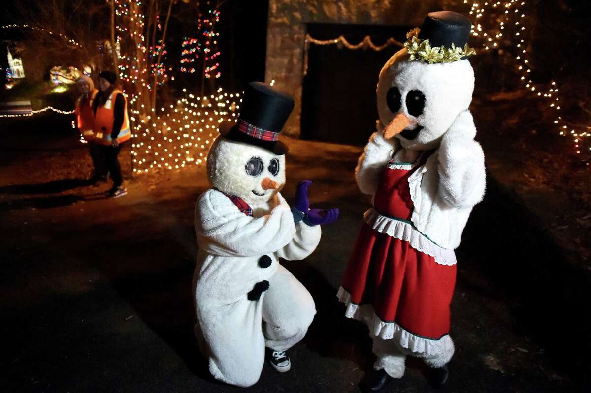 Marching Rams clarinet players Olivia Idzikowski, 14, as Frosty, left, and Celine Gustas, 16, as Mrs. Frosty, pose for carloads of spectators during the 17th annual Light up the Sky with the Marching Rams holiday light display on Thursday, Dec. 10, 2015, at 154 Brookside Ave. in Amsterdam, N.Y. The show runs through Dec. 23 from 6:30 to 9 p.m., weather permitting. The cost is $5 per vehicle with all proceeds benefitting the Amsterdam High marching band. (Cindy Schultz / Times Union)