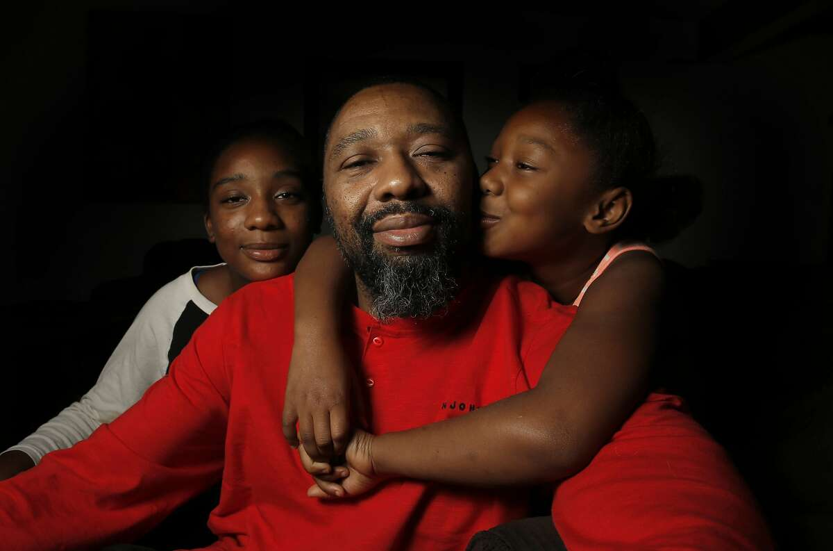 Bruce Williams with two of his three daughters Corrine, 14 and Ava, 7 at their Concord, Calif., home on Thursday December 10, 2015. Bruce has battled cancer recently and now the cancer has returned.