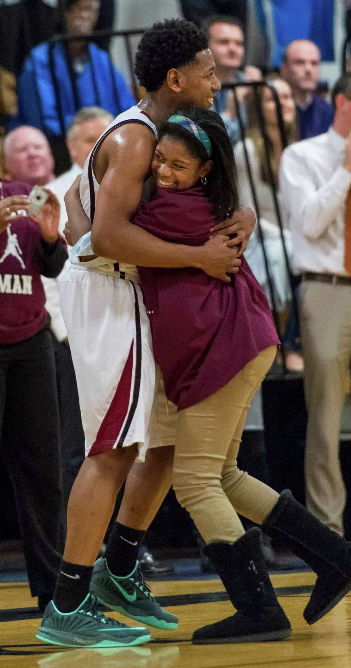 St Luke's School's Jalen Latta gets a hug from his sister, Jordan, after Jalen scored his 1,000th career point during Thursday's game against King School at the King School gym.