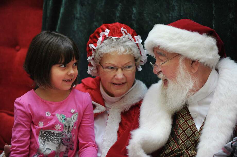 "Zoey Ehrig, 6, of Jackson, Mich., tells Santa and Mrs. Claus what she wants for Christmas at Briarwood Mall in Ann Arbor, Mich.,  Sunday, Dec. 6, 2015. Amid the dim lights and quiet of the closed shopping center, 30 families with autistic children visit Santa and Mrs. Claus (a.k.a Jim and Roxanne Albaugh)  The ""Caring Santa"" program is in its 5th year and parents say it is a blessing because their kids couldn't wait in often long lines amid screaming lights and noise.  (Brandy Baker/The Detroit News via AP) Photo: Brandy Baker, MBO / The Detroit News"