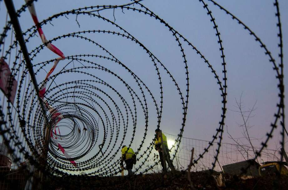 Workers take measurements of a near finished section of a  3,7 km long fence at a border crossing between Austria and Slovenia at Spielfeld, Austria on December 9, 2015. Photo: Joe Klamar, AFP / Getty Images