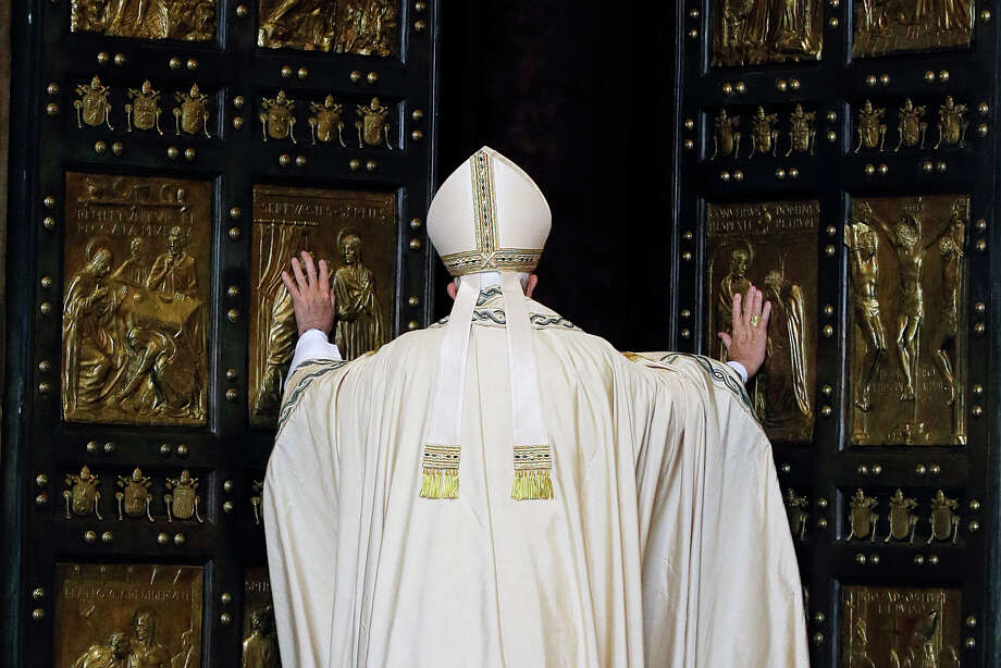 Pope Francis pushes open the Holy Door of St. Peter's Basilica, formally launching the Holy Year of Mercy, at the Vatican. Photo: Gregorio Borgia, STF / AP