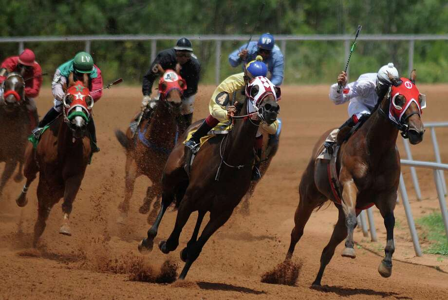 Riders and quarter horses come around the turn at the Gillespie County Fairgrounds in Fredericksburg. Texas' horse racing industry is fighting for its life and being thwarted by legislative leaders. Photo: Billy Calzada /San Antonio Express-News / © 2012 San Antonio Express-News