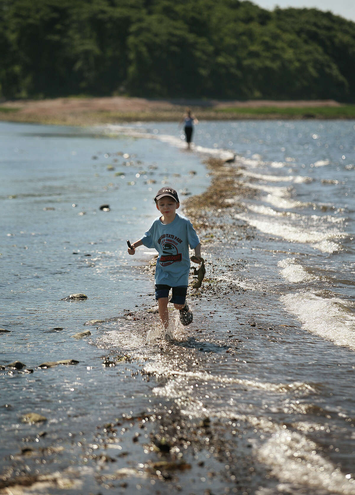 Michael Pogudin, 7, runs across the Charles Island sandbar followed by his mother, Kerry, Tuesday morning, July 5, at Silver Sands State Park in Milford. From New York, but summer residents of New Haven, the two were the last to cross ahead of the rising tide.