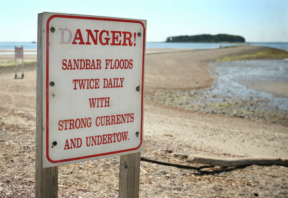 A pair of warning signs at the entrance to the Charles Island sandbar at Silver Sands State Park in Milford.