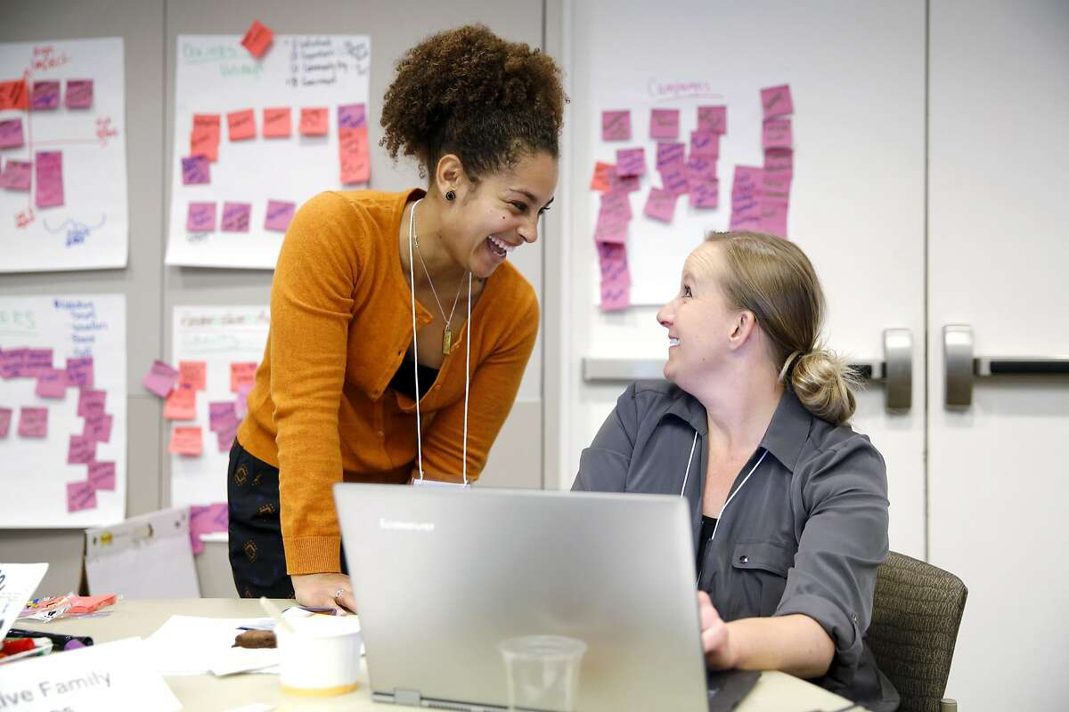 Christina Eskridge (left) of Performance Excellence talks with Jennifer Harper, director of development and marketing for Alternative Family Services, during a pro bono nonprofit workshop in Oakland, California, on Thursday, Dec. 10, 2015.