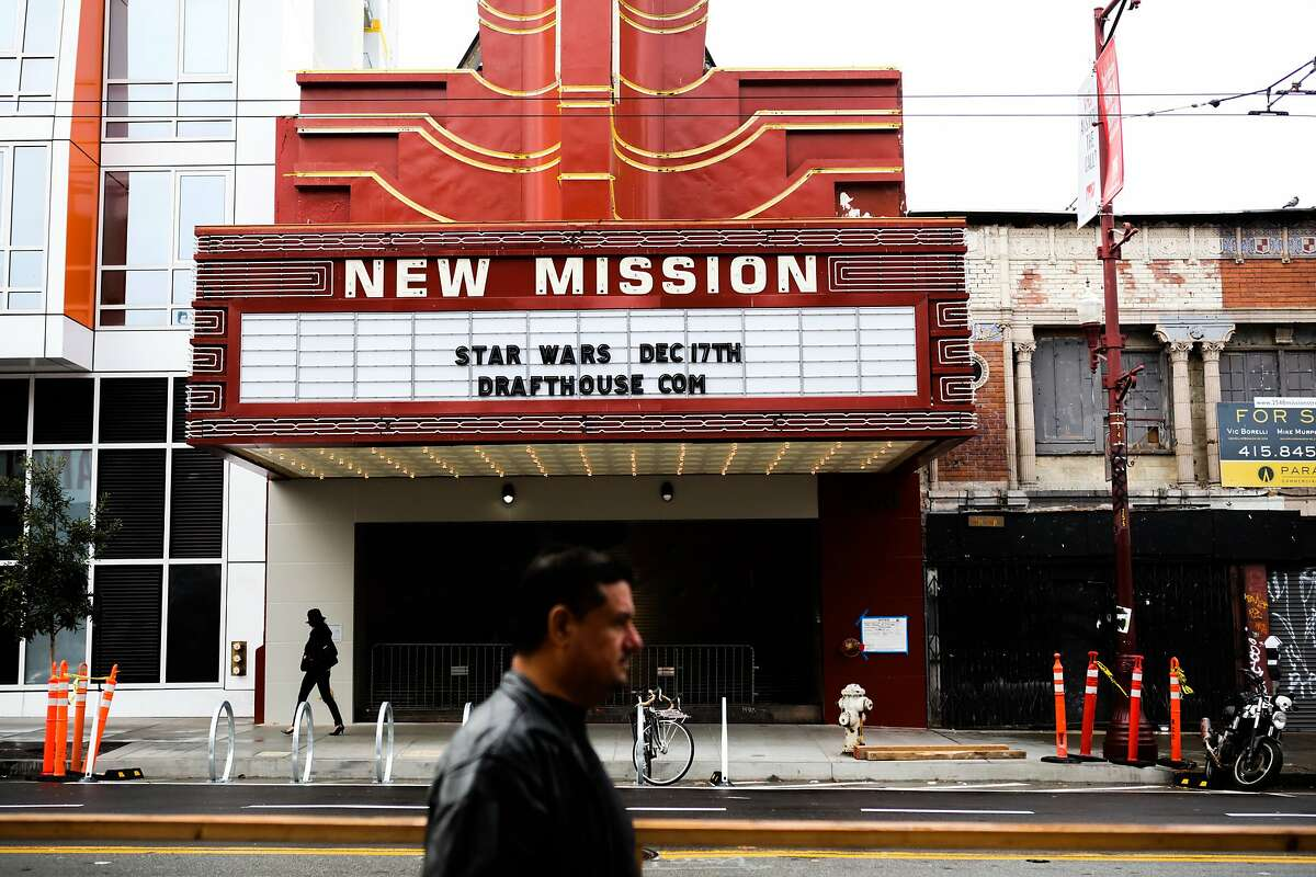 People pass the exterior marquee of the Alamo Drafthouse at the New Mission Theater in San Francisco, California on Sunday December 6, 2015. The theater is slated to open on December 17th with two premiers of the new Star Wars installment.