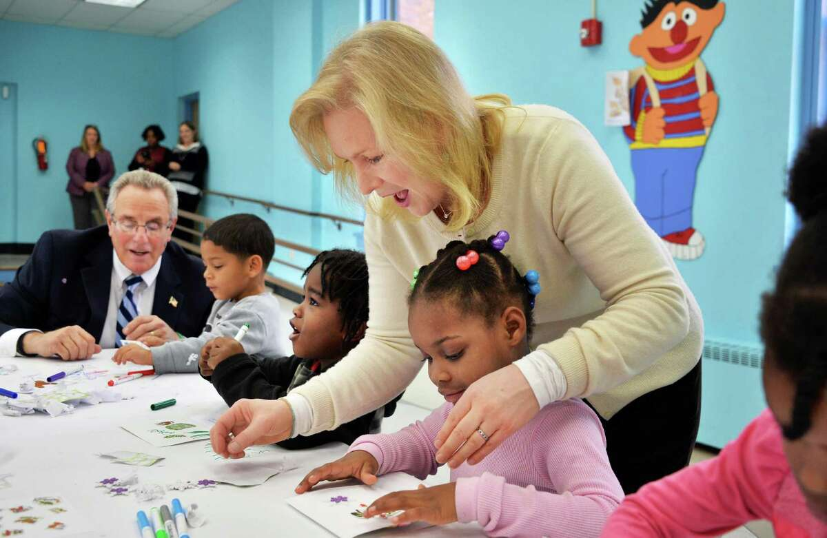Mayor Lou Rosamilia, left, and Senator Kirsten Gillibrand help children from CEO's Head Start program make holiday cards for service members stationed at Fort Drum and across the country at the Commission on Economic Opportunity's (CEO) Family Resource Center Friday Dec. 11, 2015 in Troy, NY. (John Carl D'Annibale / Times Union)