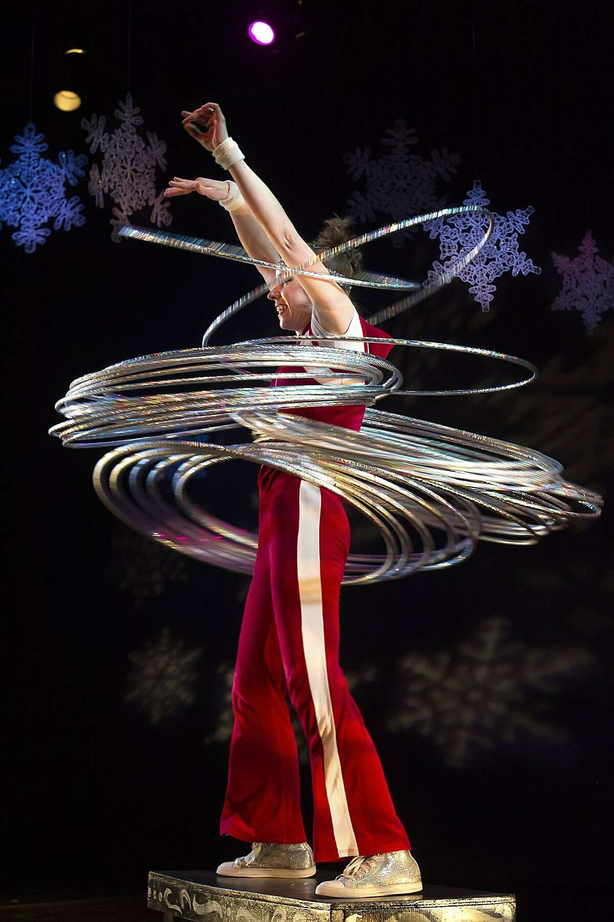 """Coventry & Kaluza 3.jpg In """"Mittens and Mistletoe: A Winter Circus Cabaret,"""" clown Natasha Kaluza manages to keep 50 hula hoops in motion. Sweet Can's family-friendly show continues through Dec. 27 at Dance Mission Theater. Photo by Shoot That Klown"""