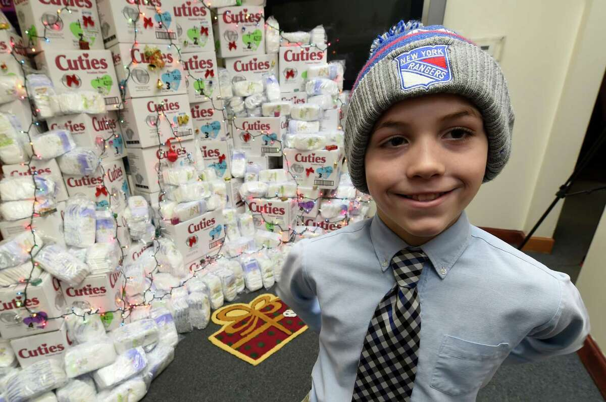 Connor Meigher, 11, student at the Albany Academy worked weekends to raise over $3500 for the homeless shows off his Rangers hockey team knit cap as he stands in front of a display of some of the items that were purchased with his donation to the Homeless and Travelers Aid Society Friday Dec. 11, 2015 in Albany, N.Y. (Skip Dickstein/Times Union)