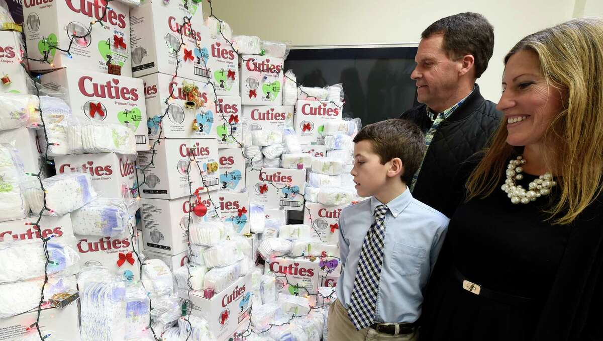 Connor Meigher, 11, student at the Albany Academy worked weekends to raise over $3500 for the homeless stands with his parents Tim and Jessica Meigher in front of a display of some of the items that were purchased with his donation to the Homeless and Travelers Aid Society Friday Dec. 11, 2015 in Albany, N.Y. (Skip Dickstein/Times Union)