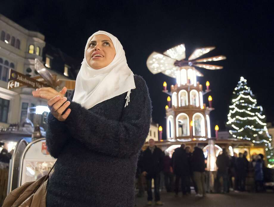 Syrian refugee Reem Habashieh stands in front of a  traditional wooden pyramid at the Christmas market in eastern Germany. Photo: Jens Meyer, Associated Press