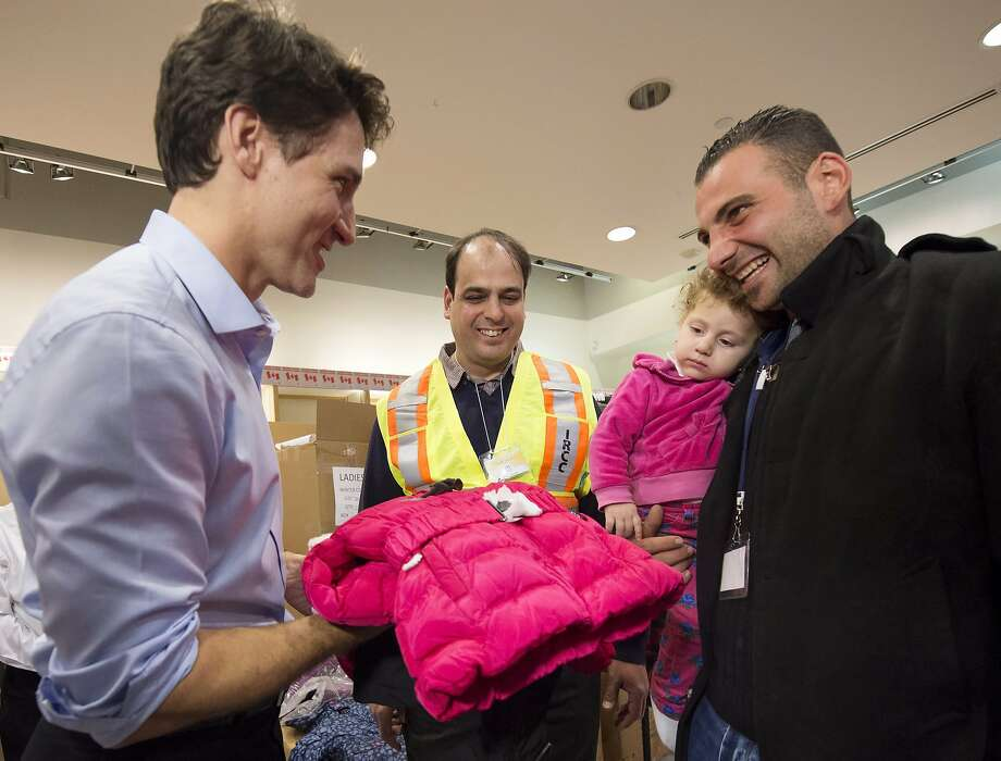 Prime Minister Justin Trudeau (left) greets Kevork Jamkossian after he and his family arrived in Toronto. Photo: Nathan Denette, Associated Press