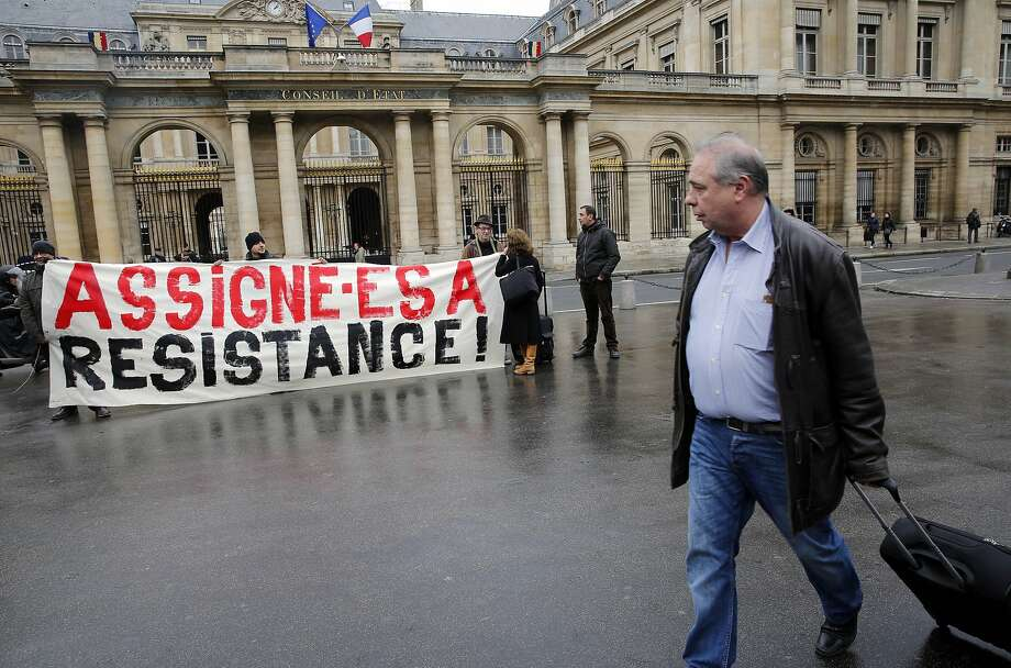 "Activists unfurl a banner reading ""Ordered to Resist"" outside France's top administrative court. Photo: Christophe Ena, Associated Press"