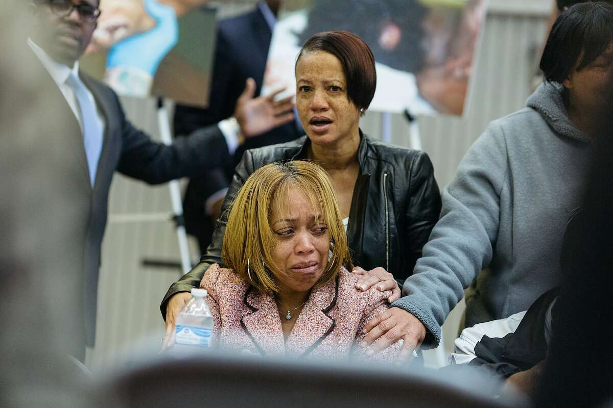 Gwen Woods, mother of Mario Woods, is consoled by unidentified individuals while the family's legal counsel displays autopsy photographs of Mario Woods who was shot and killed by SFPD on December 2, during a press conference announcing civil action at Southeast Community College in San Francisco, Calif., Wednesday, December 9, 2015.