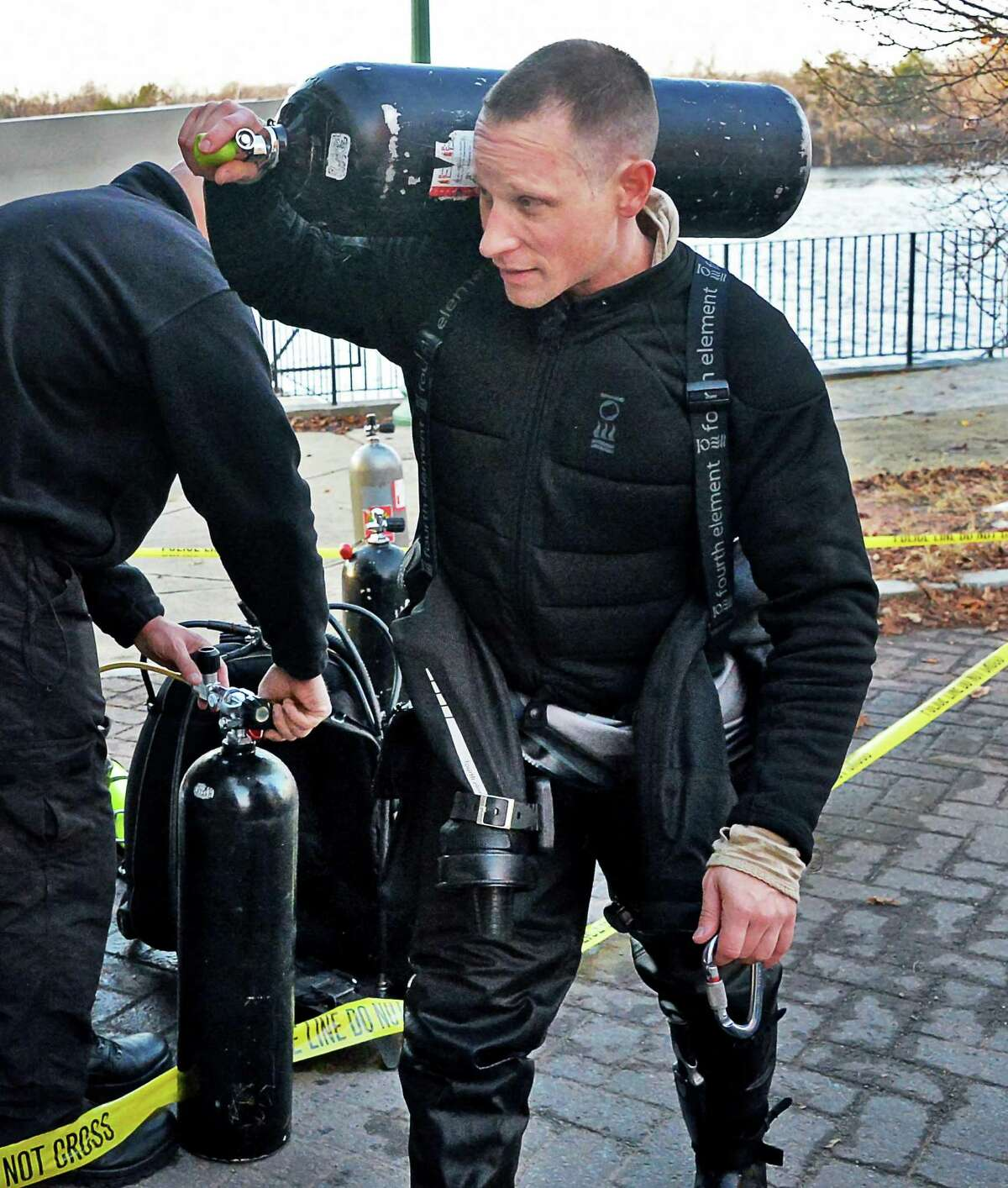 A fresh dive tank in hand, New York State Trooper Josh Cross returns to the search of the Hudson River for Noel Alkaramla Friday Dec. 11, 2015 in Troy, NY. (John Carl D'Annibale / Times Union)