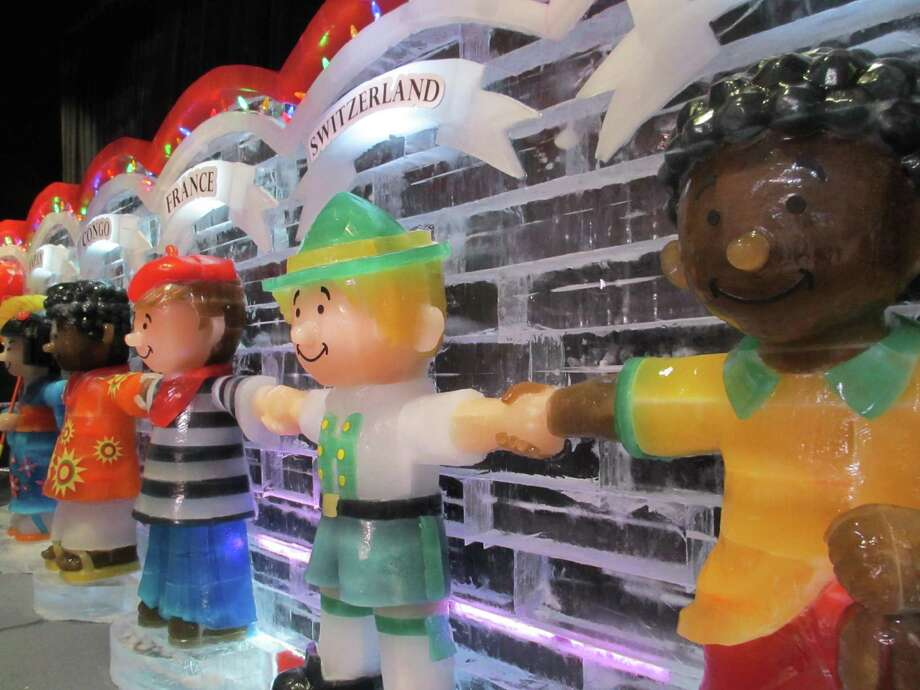 """Hand-carved characters representing countries from around the world hold hands in the """"ICE!"""" exhibit in Grapevine."""