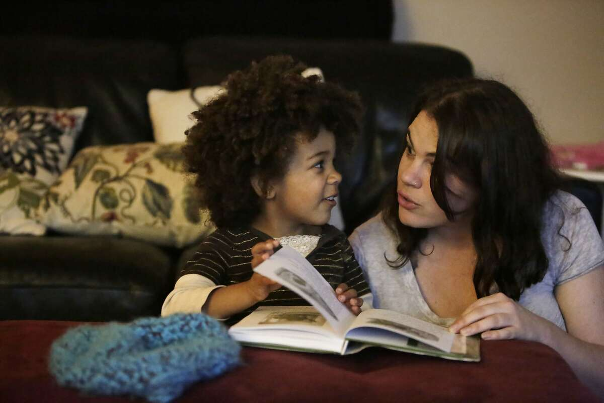 """Luella (l to r), 4, watches her mother Xana Cook-Milligan as Cook-Milligan reads her daughter a story from """"Adventures of Frog and Toad"""" as they spend time together at home on Thursday, December 10, 2015 in Pacifica, Calif."""