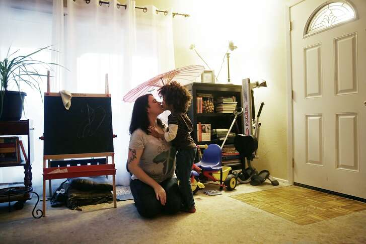 Xana Cook-Milligan (l to r) and her daughter Luella, 4, share a kiss  under a parasol as they spend time at home together on a rainy afternoon on Thursday, December 10,  2015 in Pacifica, Calif.