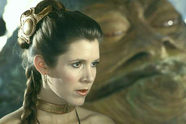 STAR WARS Trilogy.  Lucas film Ltd. & TM.   PICTURED: Carrie Fisher as Princess Leia.  HOUCHRON CAPTION (09/21/2004) SECSTAR COLORFRONT:   THE STARS: From far left, C-3PO (Anthony Daniels),(Not in picture) Princess Leia (Carrie Fisher),  Luke Skywalker (Mark Hamill), (Not in picture) Yoda (Frank Oz), (Not in picture) Chewbacca (Peter Mayhew) (Not in picture) and Han Solo (Harrison Ford) (Not in picture) are part of the Star Wars trilogy's makeover for DVD.   HOUCHRON CAPTION (05/18/2005) SECSTAR COLOR:  BEST IN BONDAGE PRINCESS LEIA ORGANA: After she was unleashed, Leia became the youngest Senator ever in the Imperial Senate. (More disturbing than the metal collar was Her Worship's ultra-friendly relationship with brother Luke.)