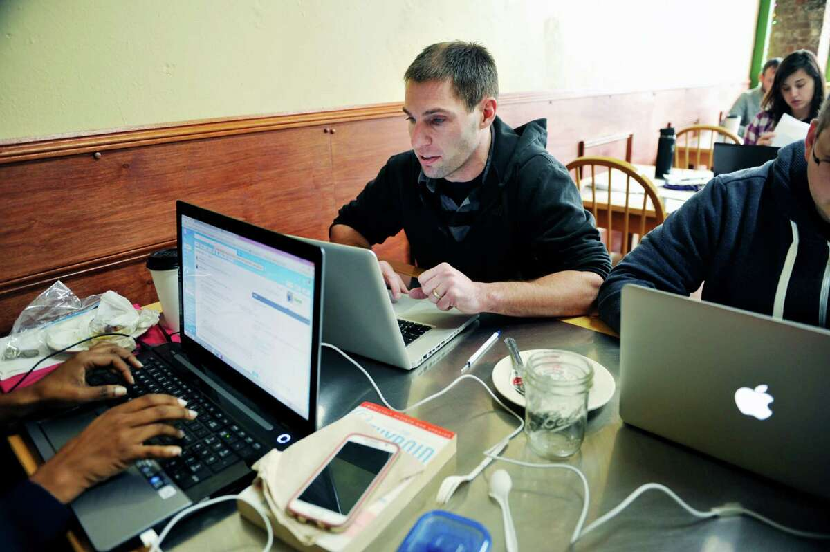 Jonathan Hentrich, lead pastor of Christ's Church Albany, works with other members of the church at Tierra Coffee Roasters on Tuesday, Dec. 8, 2015, in Albany, N.Y. (Paul Buckowski / Times Union)