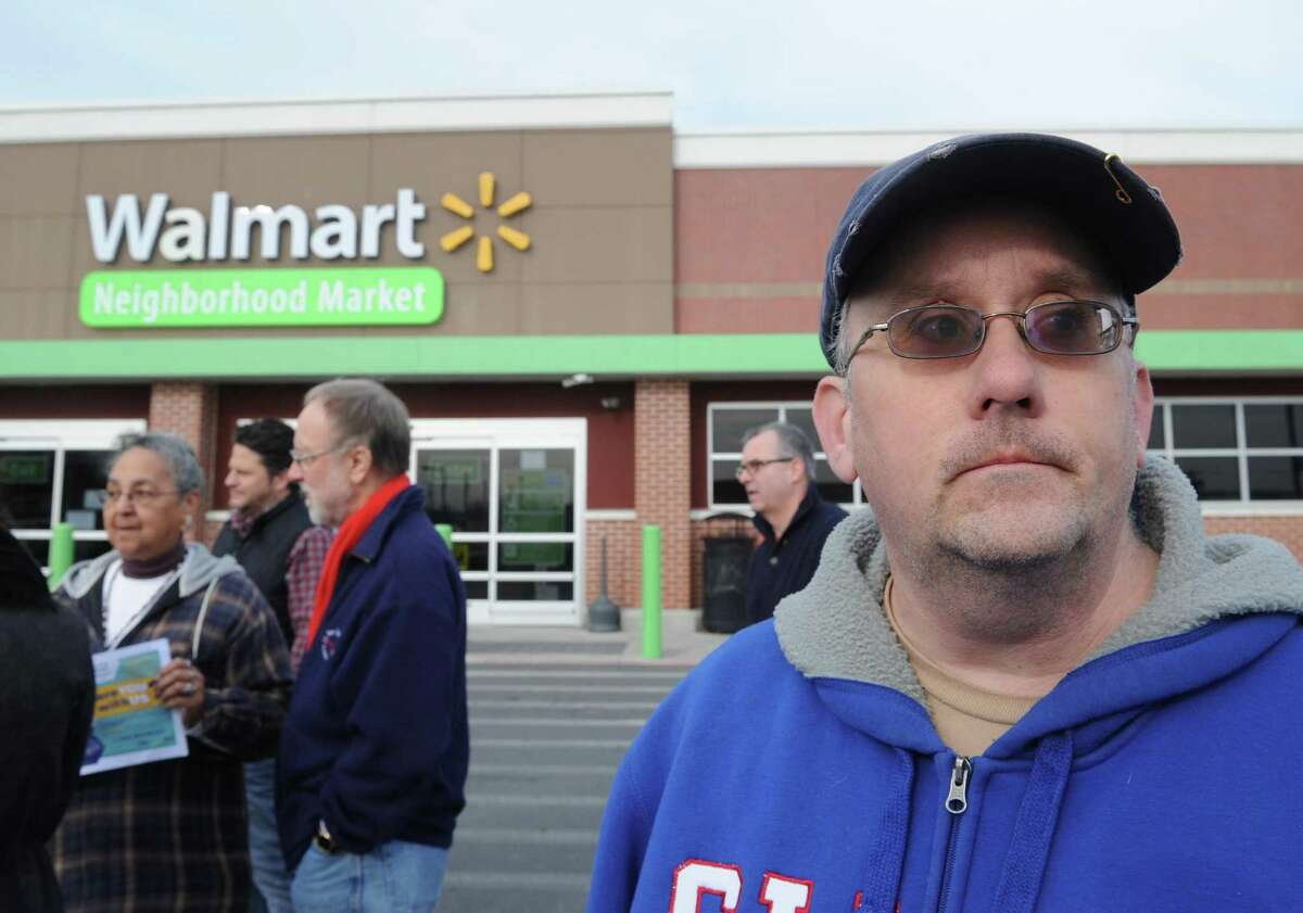 Michael Walsh of Schenectady, who was fired from this Wal-Mart on Nov. 6 for waiting 30 minutes before turning in $350 cash he found in the parking lot, takes part in a rally led by national group, Making Change at Walmart UFCW on Friday Dec. 11, 2015 in Niskayuna, N.Y. (Michael P. Farrell/Times Union)