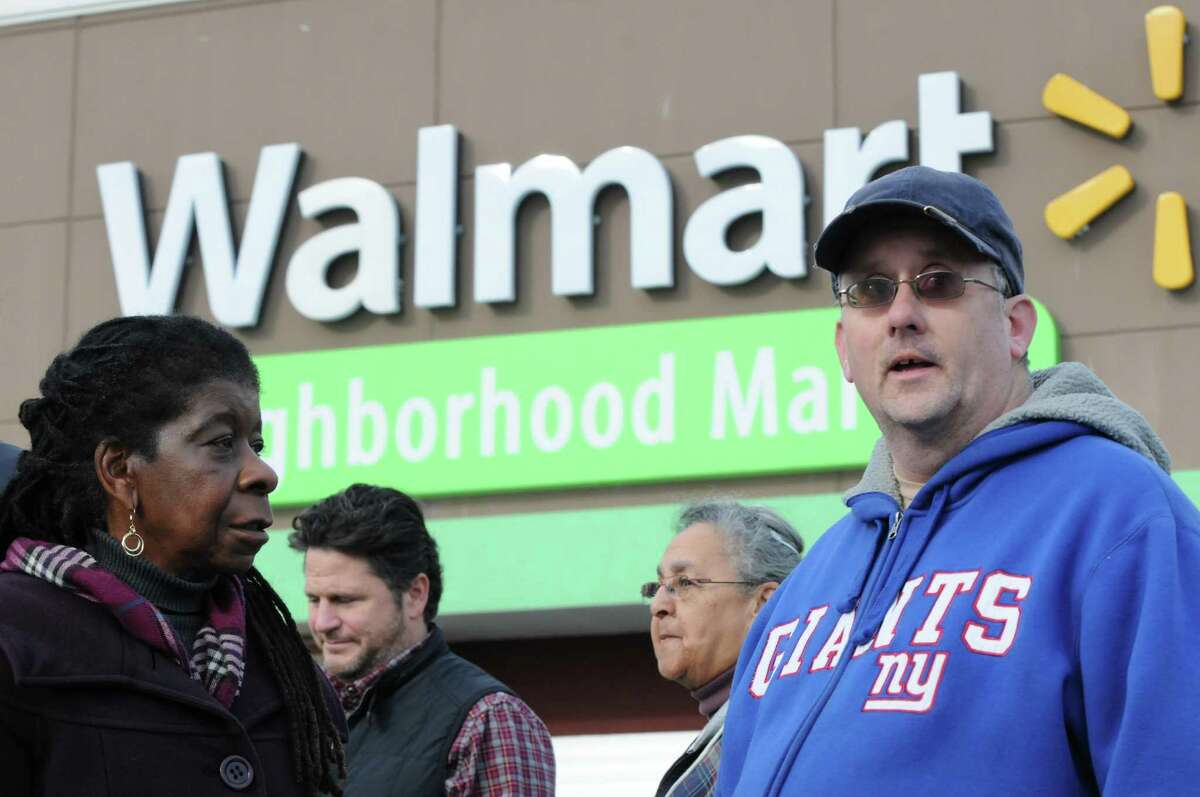 Michael Walsh, right,of Schenectady, who was fired from this Wal-Mart on Nov. 6 for waiting 30 minutes before turning in $350 cash he found in the parking lot, talks with Alice Greene during a during a rally led by national group, Making Change at Walmart UFCW on Friday Dec. 11, 2015 in Niskayuna, N.Y. (Michael P. Farrell/Times Union)