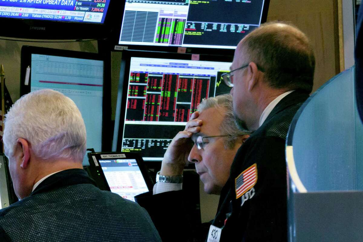 Trader Thomas Kay, center, works with colleagues at their booth on the floor of the New York Stock Exchange, Friday, Dec. 11, 2015. Stocks are sharply lower in midday trading, led by more declines in energy and materials stocks as prices for oil and other commodities slide. (AP Photo/Richard Drew)) ORG XMIT: NYRD109