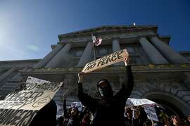 A protester holds up a sign while students from several high schools express their frustration towards police brutality at City Hall in San Francisco on Friday, December 11, 2015.