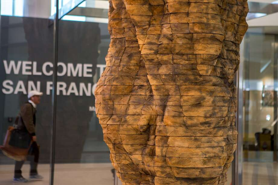 A passenger leaving the terminal passes an installation by artist Ursula von Rydingsvard at San Francisco International Airport on Thursday, Dec. 10, 2015 in San Francisco, Calif. Photo: Nathaniel Y. Downes, The Chronicle