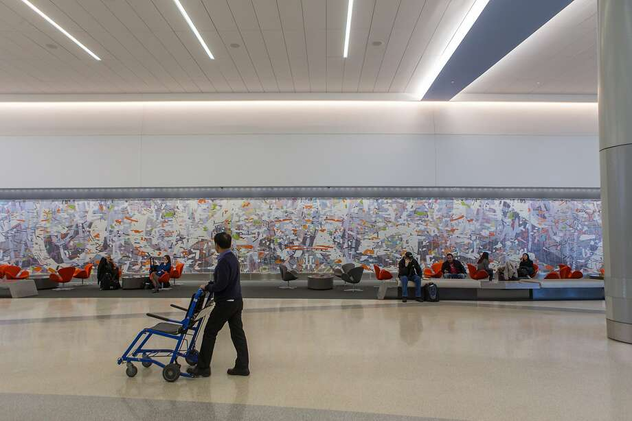 A man pushing a wheel chair looks at the 109-foot installation by artist Amy Ellingson at San Francisco International Airport on Thursday, Dec. 10, 2015 in San Francisco, Calif. Photo: Nathaniel Y. Downes, The Chronicle
