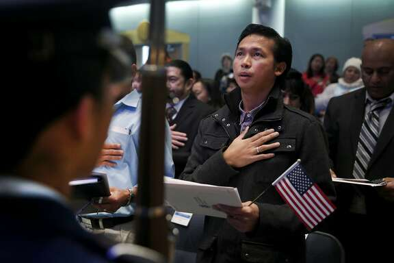 Philippines-born John Paul Intal takes the Oath of Allegiance to become a new U.S. citizen at a naturalization ceremony in Hayward, Calif. on Friday, Dec. 11, 2015.
