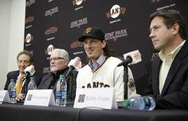 San Francisco Giants pitcher Jeff Samardzija, second from right, answers questions during a news conference Friday, Dec. 11, 2015, in San Francisco. From left to right, team president and CEO Larry Baer, executive vice president Brian Sabean and general manager Bobby Evans look on. The Giants introduced right-hander Samardzija, who signed a $90 million, five-year deal. (AP Photo/Eric Risberg)