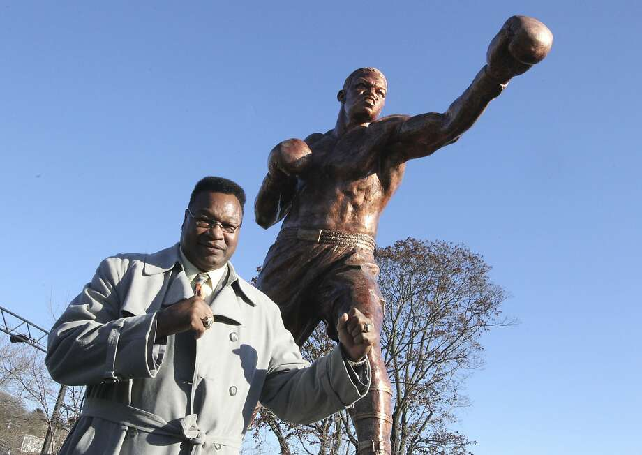 In this photo taken Monday, Dec. 7, 2015, Hall of Fame boxer Larry Holmes poses by a statue of his likeness as construction crews complete the installation of the new statue at Scott Park, where the Lehigh river runs into the Delaware in Easton, Pa. A dedication of the statue will take place Sunday, Dec. 13. (Sue Beyer/The Express-Times via AP) Photo: Sue Beyer, Associated Press