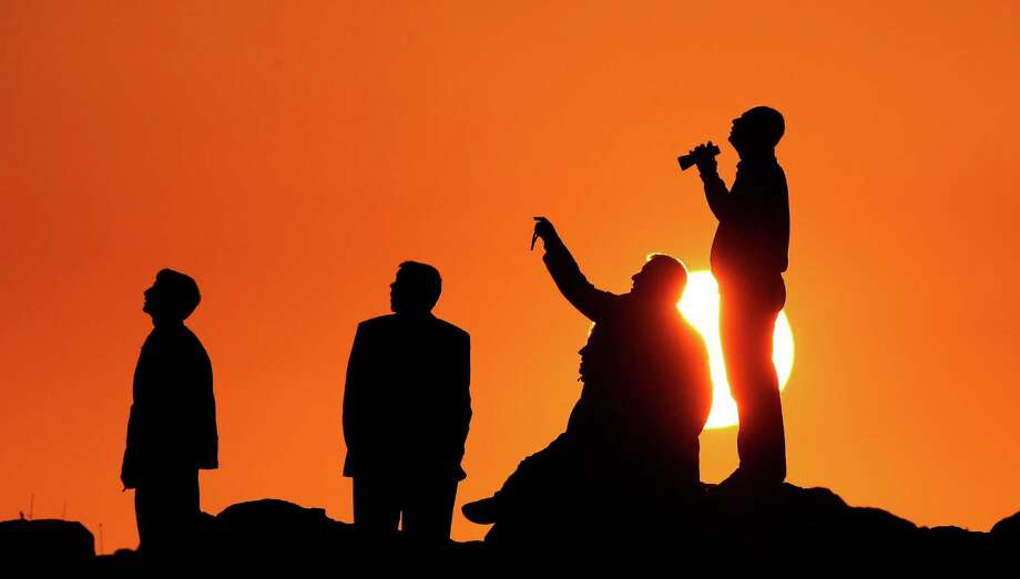 People are silhouetted on the top of a hill close to the border line between Turkey and Syria near Mursitpinar bordergate as they watch the U.S led airstrikes over the Syrian town of Kobani on October 18, 2014 in Sanliurfa, Turkey.  (Photo by Gokhan Sahin/Getty Images) Photo: Gokhan Sahin, Stringer / 2014 Getty Images