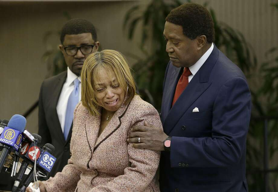 Attorney John Burris, right, comforts Gwen Woods, the mother of Mario Woods, the a knife-wielding stabbing suspect who was fatally shot by San Francisco Police last week, at a news conference at Southeast Community College in San Francisco, Friday, Dec. 11, 2015. Burris, representing the Woods family, has filed a federal civil rights and wrongful death lawsuit. (AP Photo/Jeff Chiu) Photo: Jeff Chiu, Associated Press