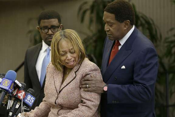 Attorney John Burris, right, comforts Gwen Woods, the mother of Mario Woods, the a knife-wielding stabbing suspect who was fatally shot by San Francisco Police last week, at a news conference at Southeast Community College in San Francisco, Friday, Dec. 11, 2015. Burris, representing the Woods family, has filed a federal civil rights and wrongful death lawsuit. (AP Photo/Jeff Chiu)