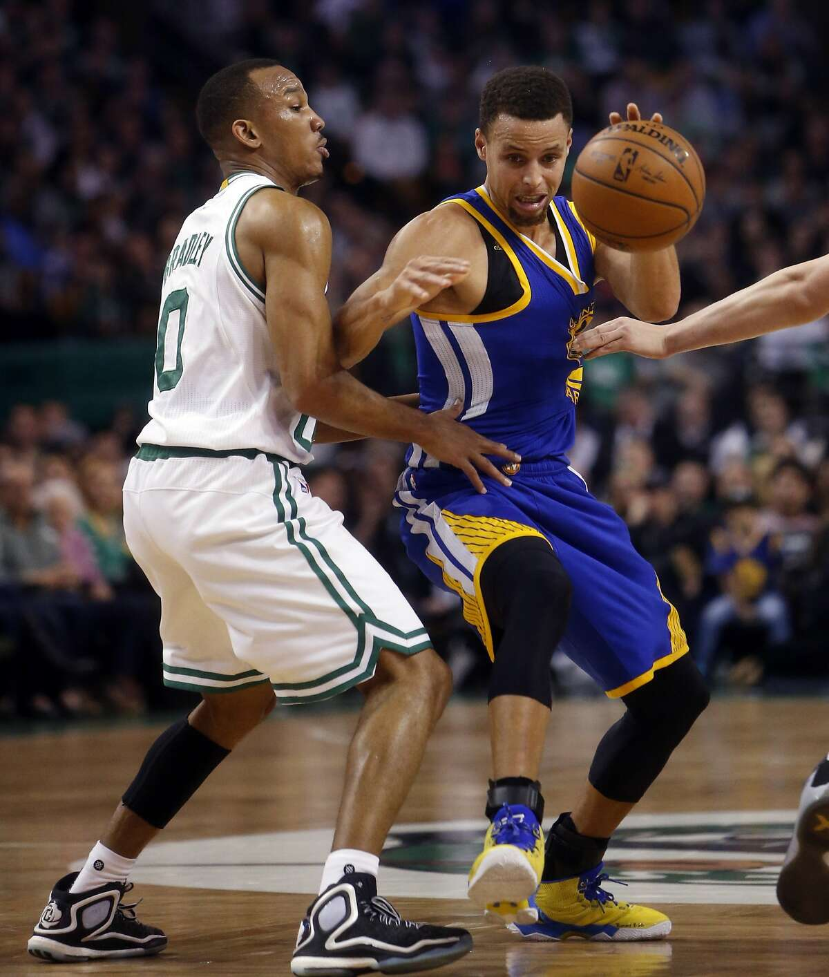 Golden State Warriors' Stephen Curry is guarded by Boston Celtics' Avery Bradley in 2nd quarter during NBA game at TD Garden in Boston, Massachusetts on Friday, December 11, 2015.