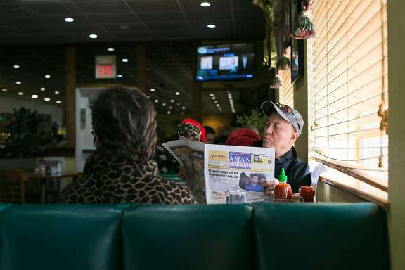 Manny Dacoron reads the newspaper at a booth while his food is prepared at Cafe Colma.