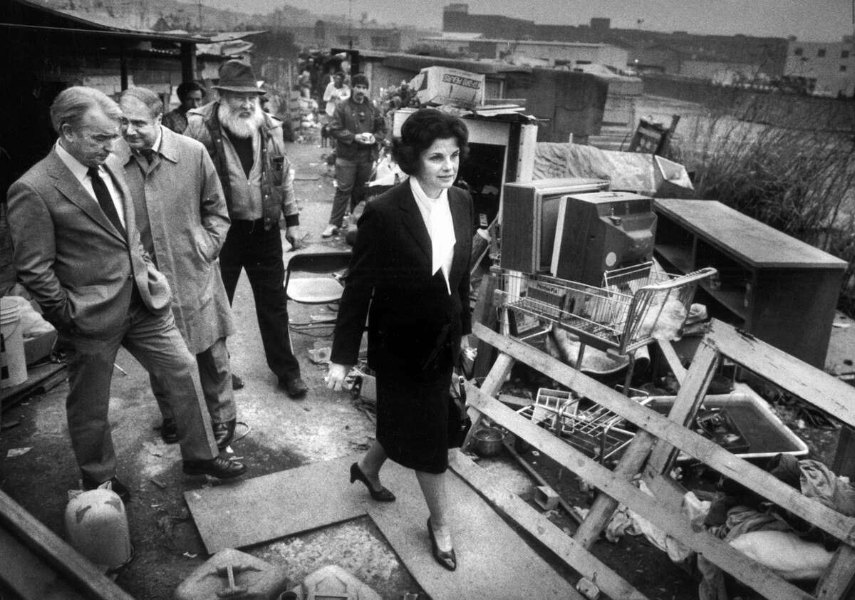 """Mayor Dianne Feinstein leads a group on a tour of Shantytown at Seventh and Berry streets in 1986. The group includes her press secretary Tom Eastham (left), Public Health Director David Werdegar and Thomas Dalton, """"mayor of Shantytown."""""""