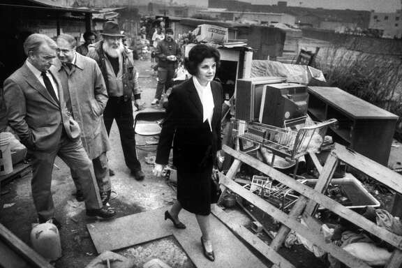 "Mayor Dianne Feinstein leads a group on a tour of Shantytown at Seventh and Berry streets in 1986. The group includes her press secretary Tom Eastham (left), Public Health Director David Werdegar and Thomas Dalton, ""mayor of Shantytown."""