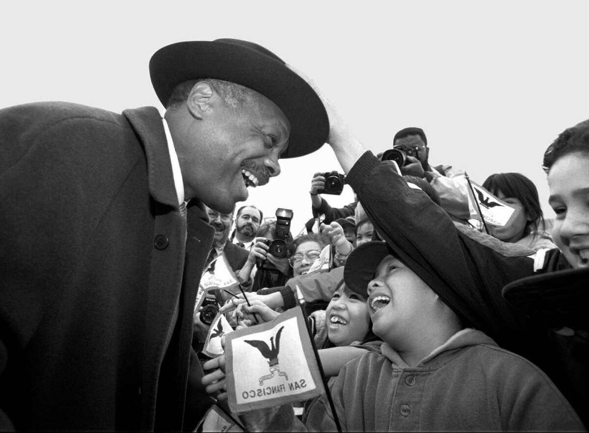 San Francisco Mayor-elect Willie Brown is greeted by schoolchildren who reach out to touch him as he makes his way into the Yerba Buena Gardens for its inaugural ceremonies in 1996. The image of the flag in the foreground is not reversed; it's seen from the back.