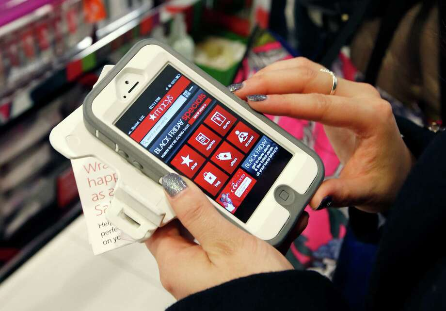 Tashalee Rodriguez, of Boston, uses a smartphone app while shopping at Macy's in downtown Boston. Though it's still a small fraction of online revenue, mobile sales are jumping too. Larger phone sizes, improved retailer apps, more online deals and shoppers increasing comfort with shopping online are driving the trend. Photo: Michael Dwyer /Associated Press / AP
