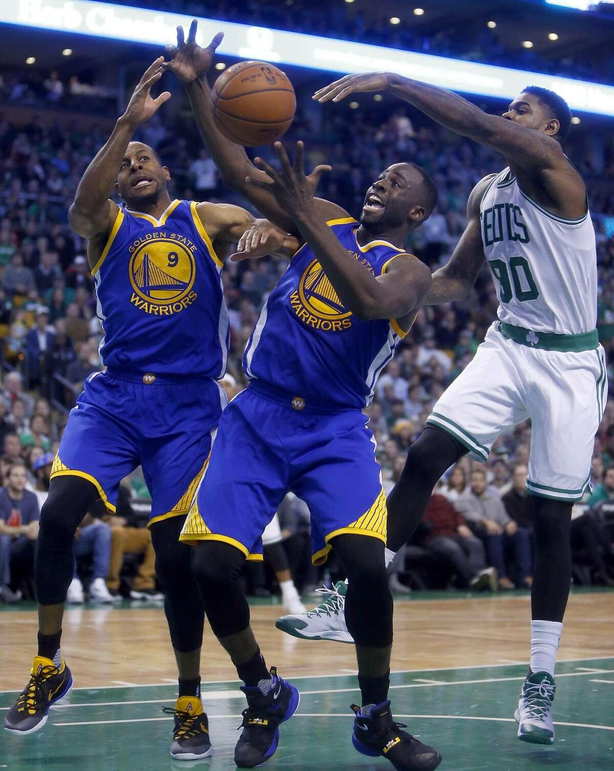 Golden State Warriors' Draymond Green and Andre Iguodala out rebound Boston Celtics' Amir Johnson during Warriors 124-119 double overtime win in NBA game at TD Garden in Boston, Massachusetts on Friday, December 11, 2015.